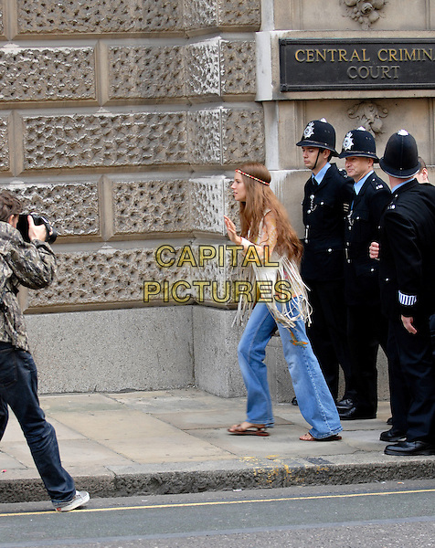"SIENNA MILLER.On the set of her new film ""Hippie Hippie Shake"", outside The Old Bailey, London, England, September 16th 2007..full length film set filmset jeans  hairband head band cream fringed tassled waistcoat costume seventies style policemen photographer.CAP/IA.©Ian Allis/Capital Pictures"