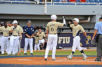 4 March 2012:  FIU infielder/outfielder Tyler James Shantz (5) celebrates his solo home-run with outfielder Nathan Burns (6) as the FIU Golden Panthers defeated the Brown University Bears, 8-3, at University Park Stadium in Miami, Florida.