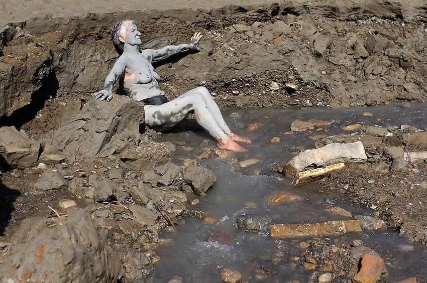 A woman covered in mud reposes in the ancient Baths of sulphurous waters of Tiermas on October 13, 2012, in the Spanish reservoir of Yesa. The ancient baths of sulphurous waters of Tiermas are under Yesa reservoir waters and return to the surface when the reservoir is running low on water.  Photo: Ander Gillenea
