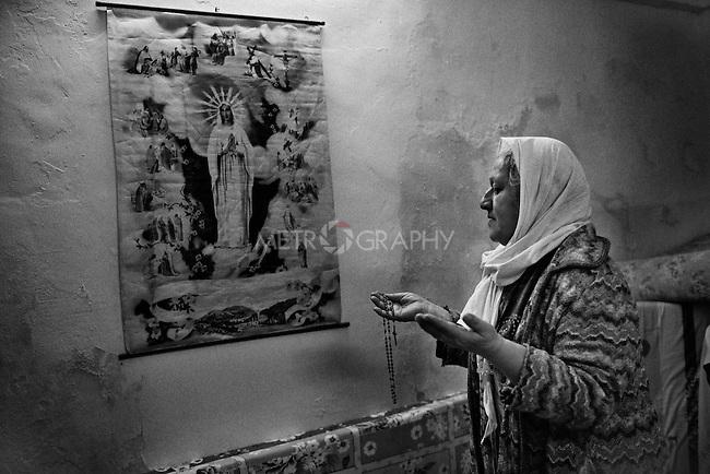 25..3.2015 Kirkuk,Iraq. Najiba is seen while praying to a Christian effigy.