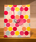 Close up of paper gift bag with circles design on wooden table surface