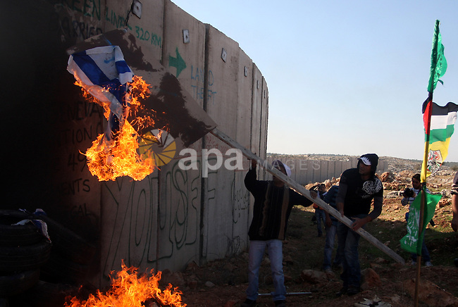 Palestinian protestors set fire the US and Israeli flags during a weekly demonstration near Israel's separation wall in the West Bank village of Nilin, on December 02, 2011. Photo by Issam Rimawi
