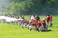 Kneeling British redcoats fire muskets during a Revolutionary War re-enactment at Fort Ticonderoga, New York, USA.