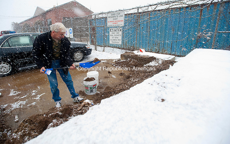 WATERBURY, CT 29 DECEMBER- 122912JS01 -Carmine Capozzi gets a couple buckets of sand from the pile outside the Waterbury Public Works building as another snow storm moves into the area on Saturday. Many parts of the area were expected to get 3-6 inches of snow. .Jim Shannon Republican American