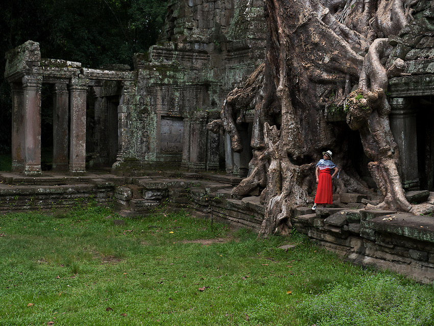Asian Tourist getting her photo taken at Ta Prohm, Ta Prohm is the modern name of the temple at Angkor, Siem Reap Province, Cambodia, built in the Bayon style largely in the late 12th and early 13th centuries.