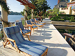 Exotic teak deck chairs are lined up in late afternoon summer sunshine on a waterfront patio.  Design by Sander Groves Landscapes, Inc., and Linda Attaway Landscape Architect.