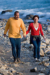 Mature couple walking on stones by beach, smiling