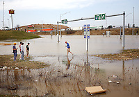 Derek Schwarzbach, 14, of of Fenton, right, walks across a flooded section of Highway 141 at the intersection of Highway 44 in Fenton Mo. on Friday, March 21, 2008. The Meramec River has risen steadily throughout the day and is expected to crest Saturday night..AP Photo/Sarah Conard