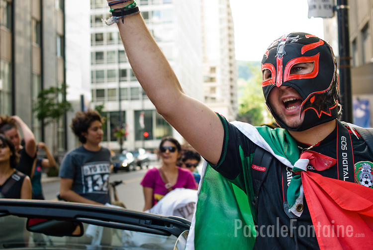 "Wearing a wrestler mask, a young mexican man protest in the street of Montreal against the ""fraudulent"" election of Enrique Pena Nieto as the new mexican president."