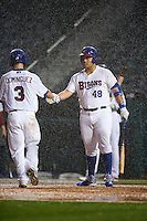 Buffalo Bisons designated hitter Jesus Montero (48) greets Matt Dominguez (3) after a home run in the pouring rain during a game against the Lehigh Valley IronPigs on July 9, 2016 at Coca-Cola Field in Buffalo, New York.  Lehigh Valley defeated Buffalo 9-1 in a rain shortened game.  (Mike Janes/Four Seam Images)