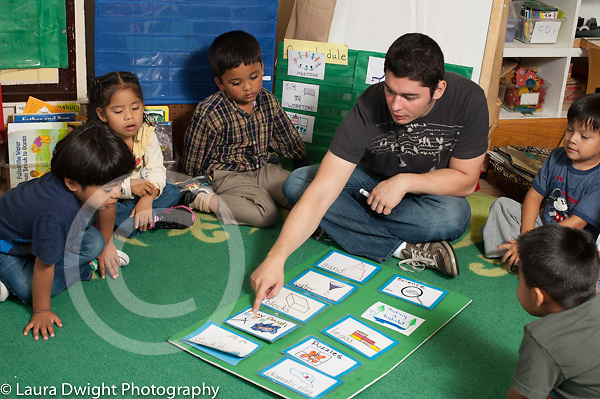 Education preschool 3-5 year olds male teacher working with group during circle time, discussing choice time activities, pointing to card with illustration and word for activity