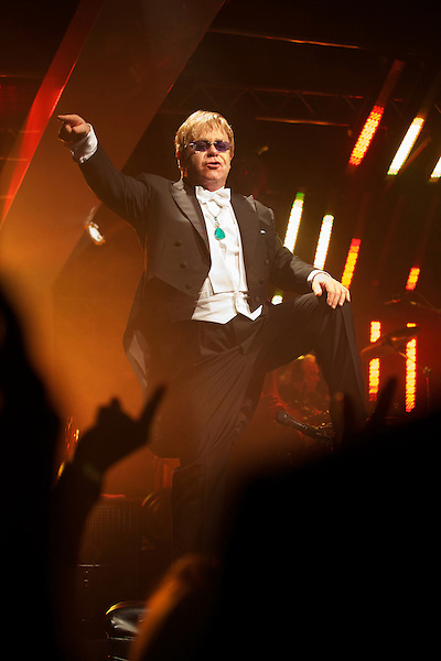Elton John sings and stands on a piano during his White Tie and Tiara Ball