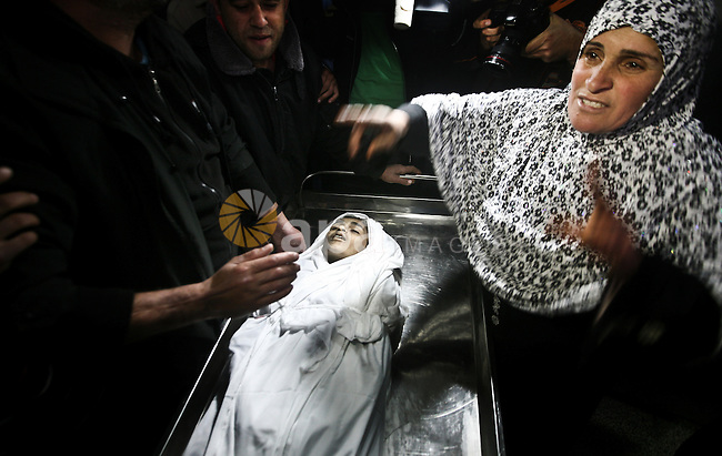 The mother of Ayoub Asalya, 12-year-old, bids fare well to her son in the morgue of Kamal Edwan hospital in Beit Lahia in the northern Gaza Strip, on March 11, 2012, following a fresh Israeli air raid, bringing the death toll from strikes since March 10 to 17 and dashing Hamas hopes of restoring a tacit truce. Photo by Ali Jadallah