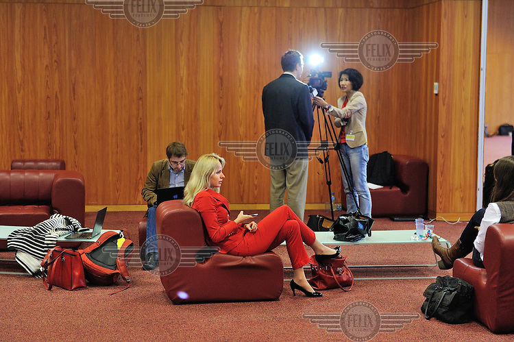 A Russian journalist wearing a red suit sits on a chair at the press center for the first round of the E3/EU+3 Iran talks in Geneva. The E3 / EU + 3 talks, which include the UK, France and Germany plus the USA, China and Russia are intended to discuss Iran's nuclear programme which Iran insists is intended for civilian purposes only while some governments in the West suspect it of having the building of a nuclear weapon as its ultimate goal.