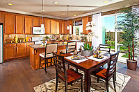 Kitchen and Dining Room with Honey Colored Cabinets and Brown Plank Style Hardwood Flooring