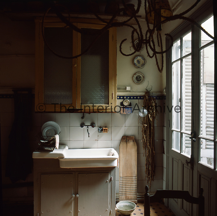 A wall mounted glass cabinet is set above a simple sink over a cupboard.