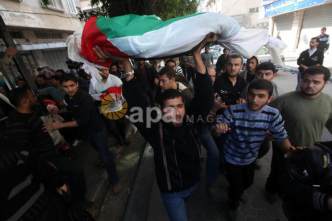 Palestinians carry the bodies of civilian from the al-Dallu family during their funeral in Gaza City, on November 19, 2012.Eleven members of the al-Dallu family were killed on Sunday when an Israeli missile struck the two-story home of the family in a residential area of Gaza City. Photo by Majdi Fathi