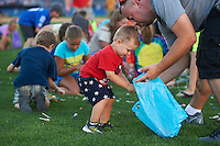 Young Batavia Muckdogs fans fill their bags during the post game helicopter candy drop after a game against the Hudson Valley Renegades on July 31, 2016 at Dwyer Stadium in Batavia, New York.  Hudson Valley defeated Batavia 4-1. (Mike Janes/Four Seam Images)
