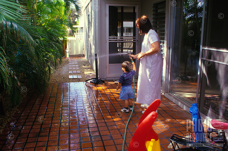Mom and son watering the yard