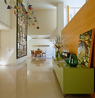 A mobile by George Rickey hangs above the polished floor in the hallway