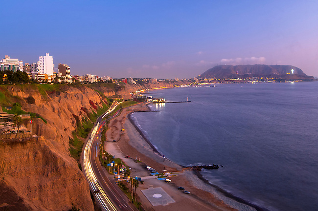 The cliffs of the Costa Verde and its Pacific beaches in the Miraflores district of Lima, Peru.  The promontory Morro Solar rises in the background.