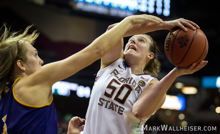 Florida State center Chatrice White scores from under the basket despite a foul from Western Illinois forward Olivia Braun during the second half of a first-round game of the NCAA women's college basketball tournament in Tallahassee, Fla., Friday, March 17, 2017. Florida State defeated Westeren Illinois 87-66. (AP Photo/Mark Wallheiser)