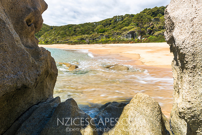 View through rock formation on Anapai Bay on Abel Tasman Coast Track, Abel Tasman National Park, Nelson Region, South Island, New Zealand
