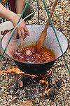 A person adds meat to the Hungarian Goulash being made over a fire, in Gyor, Hungary.