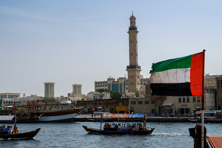 UNITED ARAB EMIRATES, DUBAI - CIRCA JANUARY 2017: The Dubai Creek in Deira and the United Arab Emirates Flag.