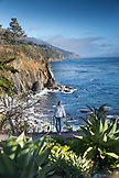 USA, California, Big Sur, Esalen, woman standing on the deck below the Murphy House with distant views of the Big Sur Coastline and the Pacific Ocean, the Esalen Institite