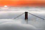 A rising sun peeked over a blanket of fog that overwhelmed the San Francisco Bay, California.