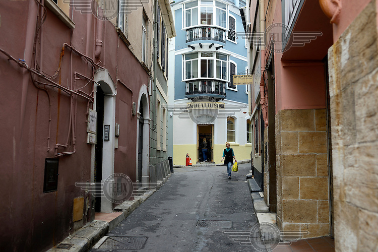 A young woman walks a narrow street.
