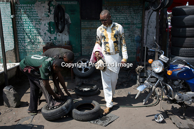"""KINSHASA, DEMOCRATIC REPUBLIC OF CONGO - FEBRUARY 11: Weston Mwene Kibambe, a Sapeur (and business man) dresses in his favorite suit at at his tire shop on February 11, 2017 in Kinshasa, DRC. The word Sapeur comes from SAPE, a French acronym for Société des Ambianceurs et Persons Élégants. or Society of Revellers and Elegant People. It also means to dress with """"elegance and style"""". Most of the young Sapeurs are unemployed, poor and live in harsh conditions in Kinshasa, a city of about 10 million people. For many of them being a Sapeur means they can escape their daily struggles and dress like fashionable Europeans. Many hustle to build up their expensive collections. Most Sapeurs could never afford to visit Paris, and usually relatives send or bring clothes back to Kinshasa. Mr. Kibambe owns a small business, a tire repair shop, and he also sells used tires. (Photo by Per-Anders Pettersson)"""
