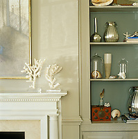 Coral and sea shells mingle with mercury glass and other objects displayed on open shelves in the living room