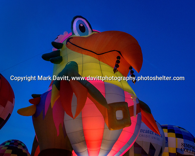 A near record crowd hot air balloon fans filled the hillsides at the National Balloon Classic launch field July 30 for a fly-in and Night Glow. Balloonist Dave Reineke of Mahomet, Illinois flies the Parrot balloon and lit up th inside of the balloon for the evening entertainment on the field.