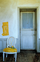 A Louis XVI chair stands against a distressed plaster wall and a pale blue doorway