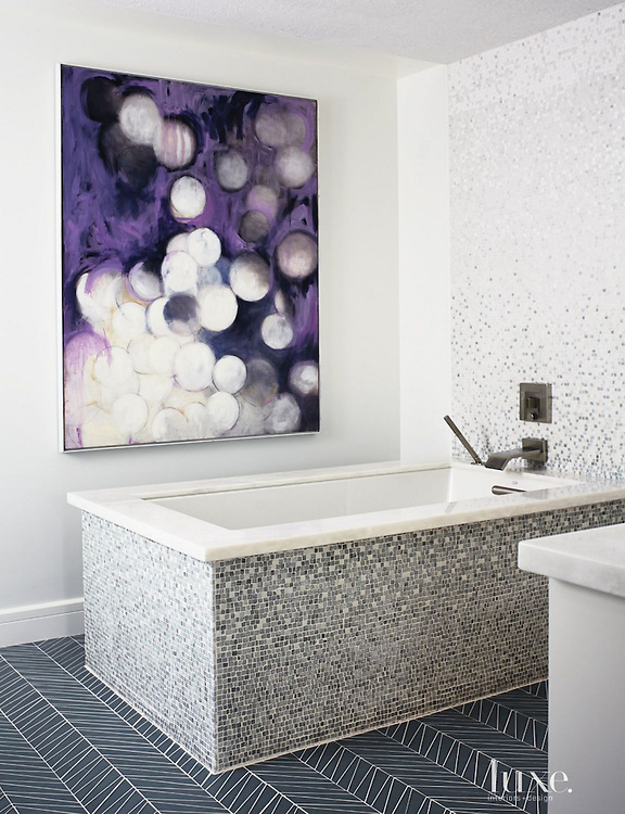 """""""Tile becomes like artwork in the master bath, where the material, in Mist Mosaic from The Fine Line, wraps a tub from Kohler, as well as a wall backing the faucet, also from Kohler. An abstract painting by Chicago artist Linc Thelen graces another wall.""""<br /> <br /> Photography by Laura Moss<br /> <br /> View the full house tour here: luxesource.com/collection/2491/45236<br /> <br /> Visit the Fine Line in Chicago for your next design project: www.finelinetile.com/"""