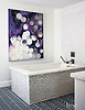"""Tile becomes like artwork in the master bath, where the material, in Mist Mosaic from The Fine Line, wraps a tub from Kohler, as well as a wall backing the faucet, also from Kohler. An abstract painting by Chicago artist Linc Thelen graces another wall.""<br />