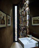 The slit window in this unusuallly shaped wet room looks out to the forest beyond