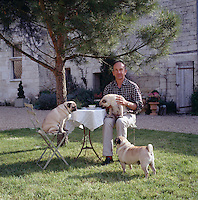 Designer David Hare sitting at a table with his three Pugs in the garden of his French country house