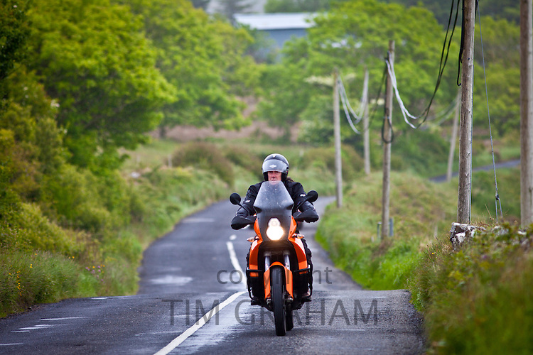 Motorcyclist in country lane in County Clare, West of Ireland
