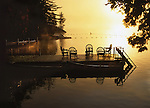 Sunsetting over a golden lake with a timber jetty with chairs