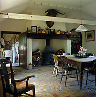 A wood-burning stove occupies the original hearth that dominates this rustic kitchen
