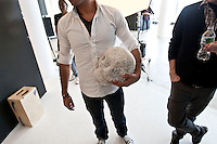 Jeweler-to-the-stars Rodrigo Otazu (C) holds a skull covered in Swarovski crystals during a photo shoot, in New York, 8 November 2009.