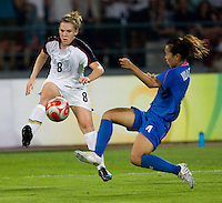 USWNT forward (8) Amy Rodriguez crosses the ball in front of Japanese defender (4) Azusa Iwashimizu while playing at Worker's Stadium.  The USWNT defeated Japan, 4-2, during the semi-finals of the Beijing 2008 Olympics in Beijing, China.