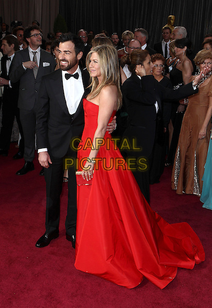 Justin Theroux & Jennifer Aniston (wearing Valentino).85th Annual Academy Awards held at the Dolby Theatre at Hollywood & Highland Center, Hollywood, California, USA..February 24th, 2013.oscars full length black tuxedo white shirt bow tie beard facial hair red strapless dress gown couple engaged silver clutch bag side profile .CAP/ADM/SLP/COL.©Colin/StarlitePics/AdMedia/Capital Pictures