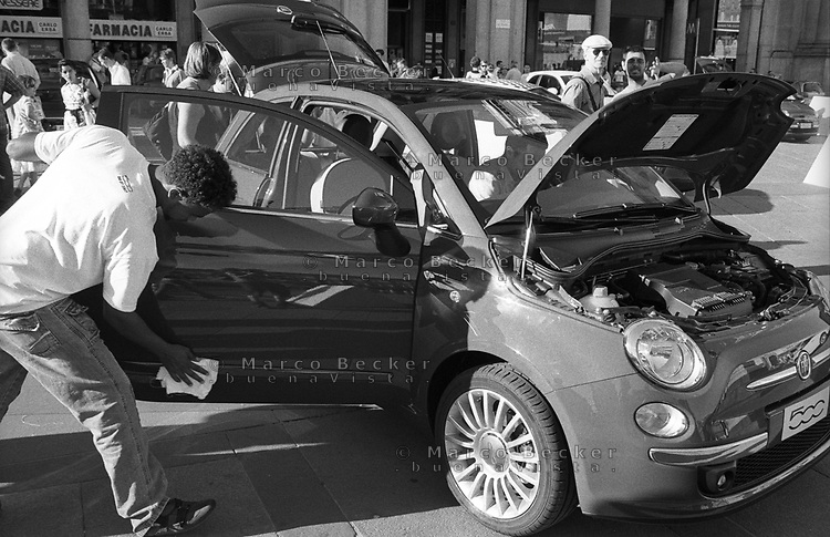 Milano, esposizione in piazza Duomo della nuova FIAT 500. Un ragazzo di colore addetto alla pulizia delle vetture --- Milan, exposition in Duomo square of the new FIAT 500. A black guy working as cleaning man for the vehicles