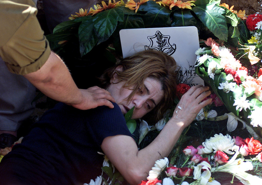 The mother of slain soldier Sgt. Ofir Kit, collapses from grief on his grave at his funeral in Jerusalem's Mt. Herzel Military cemetery June 24, 2001. Kit was killed with another soldier in an explosion in the Gaza Strip on Friday. The soldiers were lured toward a booby-trapped jeep by Palestinians calling for help, the army said.