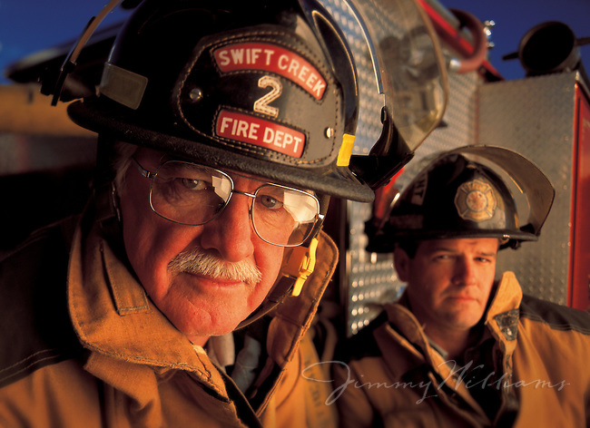 An older fireman and his son stand in front of the firetruck they use in full uniform.