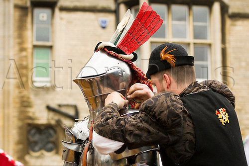 20.06.2015.  Peterborough, England. Peterborough Joust of St Peter.   A knight's squire tightens his knight's helmet.  The joust took place at Peterborough Cathedral and was the first full medieval joust in a city for 500 years. The joust was part of the Peterborough Heritage Festival 2015.